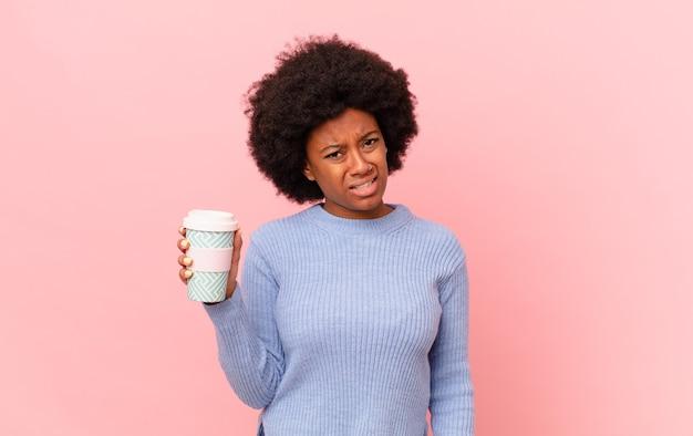 Donna afro che si sente perplessa e confusa, con un'espressione stupida e stordita guardando qualcosa di inaspettato. concetto di caffè