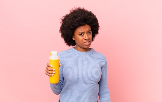 Donna afro che si sente perplessa e confusa, con un'espressione stupida e stordita guardando qualcosa di inaspettato. concetto di frullato