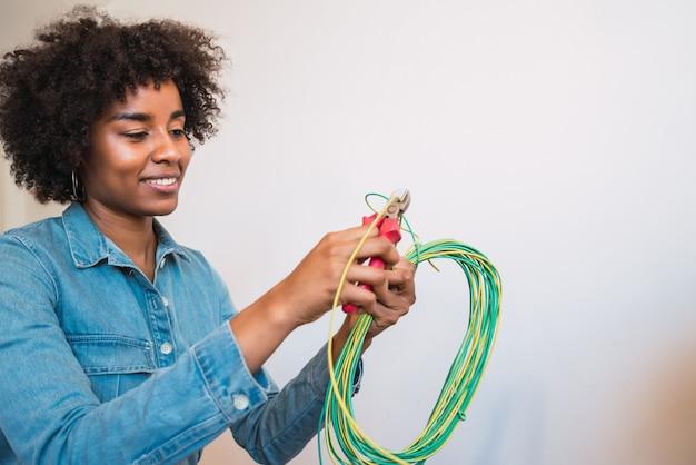Donna afro che ripara problema di elettricità a casa.