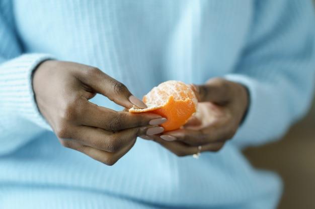 Mani della donna afro che sbucciano il mandarino dolce maturo, indossano un maglione blu, si chiudono. frutta invernale, alimentazione sana, natale