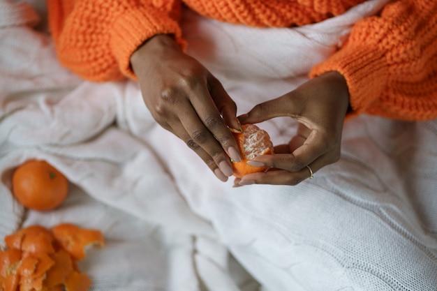 Mani di donna afro sbucciare il mandarino dolce maturo, indossare un maglione arancione, sdraiato a letto sotto il plaid