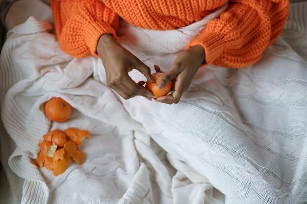 Mani di donna afro che sbucciano il mandarino dolce maturo, indossano un maglione arancione, sdraiato a letto sotto il plaid bianco lavorato a maglia. frutta invernale, concetto di natale.