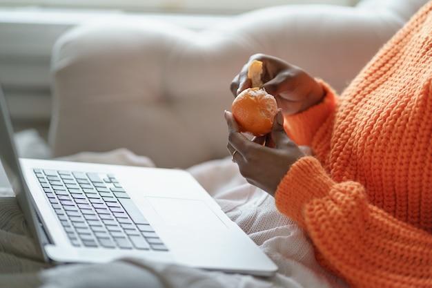 Mani di donna afro che sbucciano il mandarino dolce maturo, indossano un maglione arancione, lavorando al computer portatile a casa