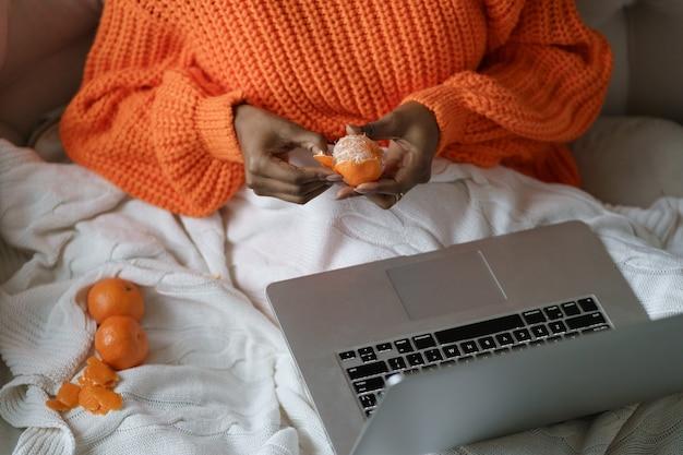 Mani della donna afro che sbucciano il mandarino dolce maturo, indossano un maglione arancione