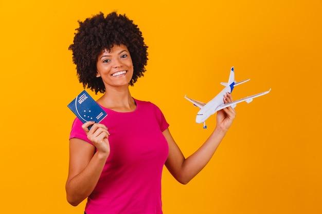 Donna afro che tiene un aeroplano giocattolo e un passaporto brasiliano. donna conceptafro di viaggio che tiene un aeroplano del giocattolo e un passaporto brasiliano. concetto di viaggio