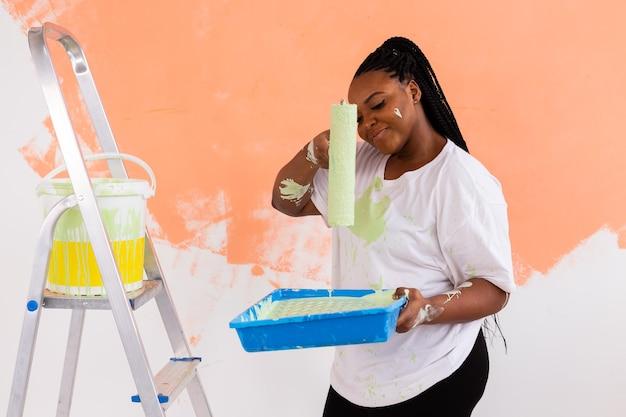 Donna afro che dipinge le pareti della nuova casa. concetto di ristrutturazione, riparazione e ristrutturazione.