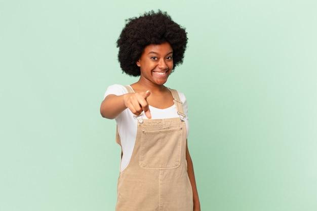 Donna afro che punta alla telecamera con un sorriso soddisfatto, fiducioso e amichevole, scegliendo il tuo concetto di chef