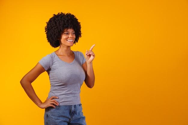 Donna afro che punta sul giallo con spazio per il testo
