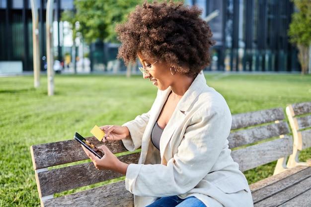 Donna afro che fa shopping online con cellulare e carta di credito