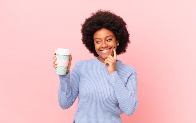 Donna afro che sorride felicemente e sogna ad occhi aperti o dubita, guardando di lato. concetto di caffè