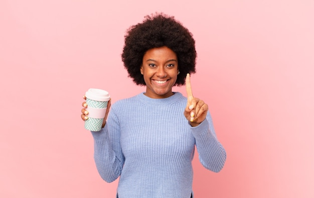 Donna afro sorridente e dall'aspetto amichevole, mostrando il numero uno o prima con la mano in avanti, conto alla rovescia. concetto di caffè