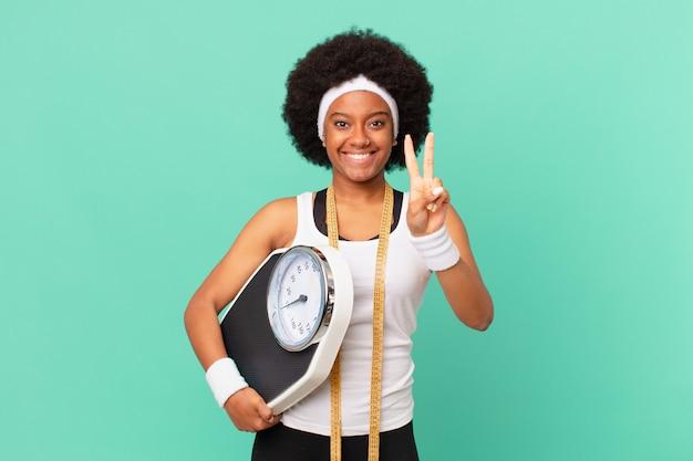 Donna afro sorridente e dall'aspetto amichevole, mostrando il numero due o il secondo con la mano in avanti, conto alla rovescia concetto di dieta