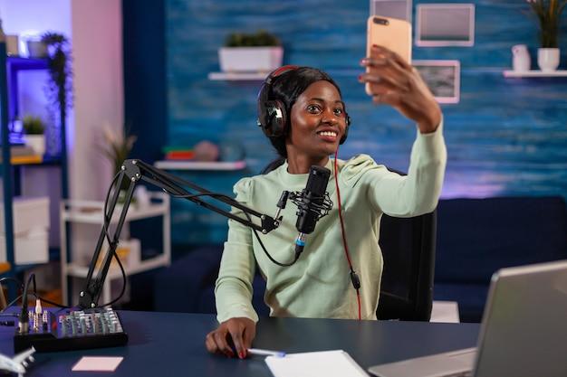 Donna afro che si fa selfie con lo smartphone e utilizza attrezzatura professionale per registrare un episodio in salotto. podcast online di produzione online in onda mostra host in streaming di contenuti live, registrazione di social digitali