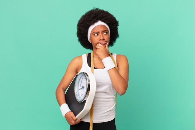 Donna afro che pensa, si sente dubbiosa e confusa, con diverse opzioni, chiedendosi quale decisione prendere per il concetto di dieta