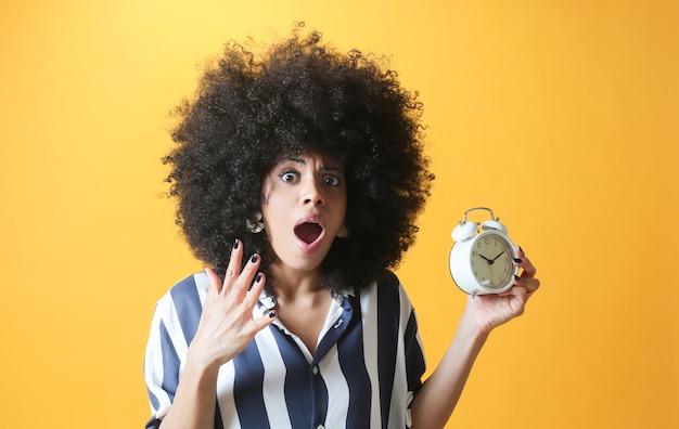 Donna afro, con sveglia e faccia spaventata