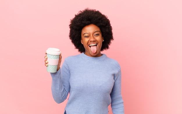 Donna afro con atteggiamento allegro, spensierato, ribelle, scherzando e tirando fuori la lingua, divertendosi. concetto di caffè