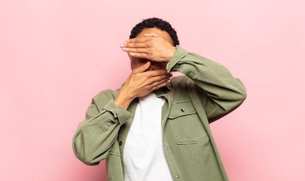 Afro giovane donna di colore che copre il viso con entrambe le mani dicendo no alla telecamera! rifiutare le foto o vietare le foto
