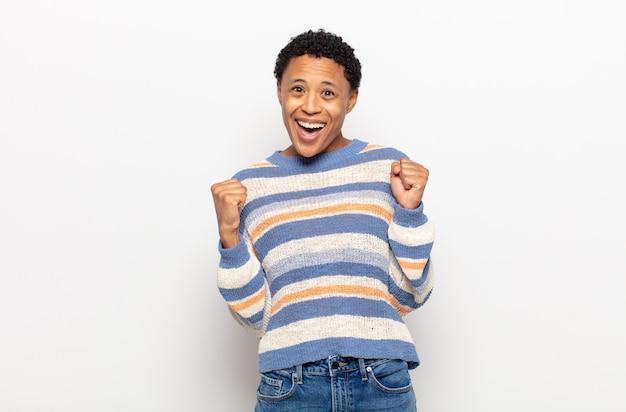 Afro giovane donna di colore che si sente felice, rilassata e soddisfatta, mostrando approvazione con gesto ok, sorridendo