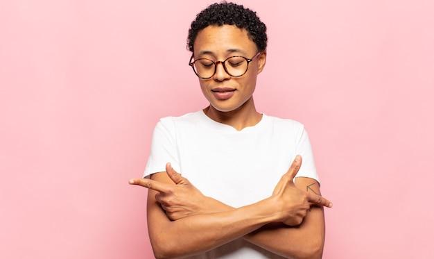 Afro giovane donna di colore che sembra perplessa e confusa, insicura e punta in direzioni opposte con dubbi