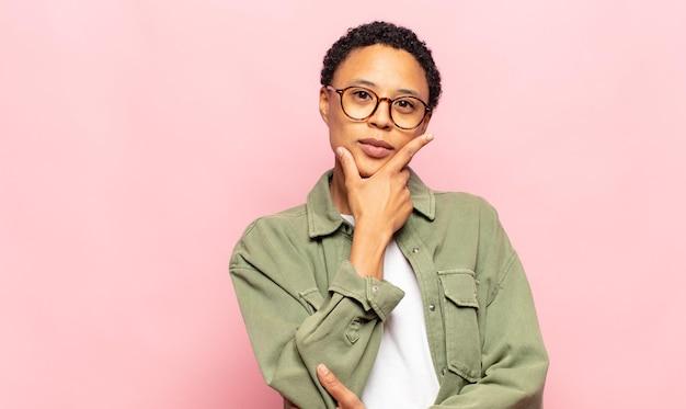 Afro giovane donna nera che sembra seria, premurosa e diffidente, con un braccio incrociato e la mano sul mento, opzioni di ponderazione