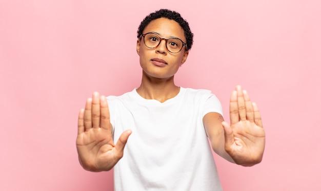 Afro giovane donna di colore che sembra seria, infelice, arrabbiata e scontenta che vieta l'ingresso o che dice stop con entrambi i palmi aperti