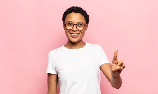 Afro giovane donna nera sorridente e guardando amichevole, mostrando il numero uno o il primo con la mano in avanti, il conto alla rovescia