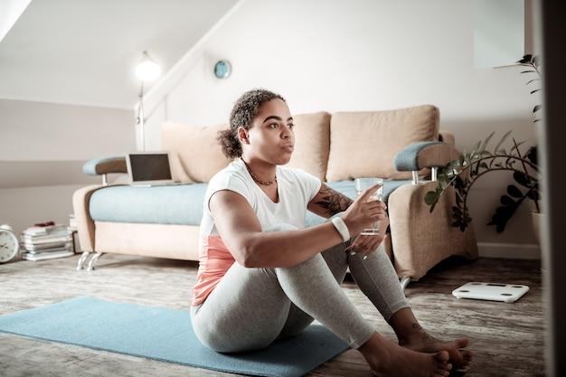 Dopo l'allenamento attivo. signora riccia afroamericana che si siede sulla stuoia di yoga e acqua potabile chiusa in se stessa