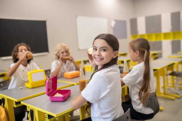 Dopo la lezione. scolari che pranzano in classe e sembrano felici