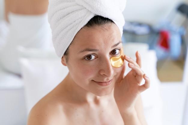 Dopo la doccia, la ragazza viene avvolta in un asciugamano e indossa cerotti cosmetici per la pelle sotto gli occhi. procedure cosmetiche a casa