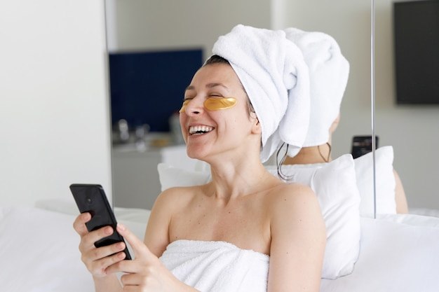 Dopo la doccia, la ragazza viene avvolta in un asciugamano e indossa cerotti cosmetici per la pelle sotto gli occhi. guarda il cellulare. procedure cosmetiche a casa. prepararsi per un appuntamento