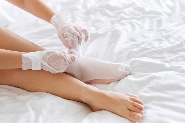 Dopo una doccia, una ragazza avvolta in un asciugamano usa guanti cosmetici per idratare la pelle delle mani e dei piedi. tendenze cosmetiche per la cura del corpo a casa