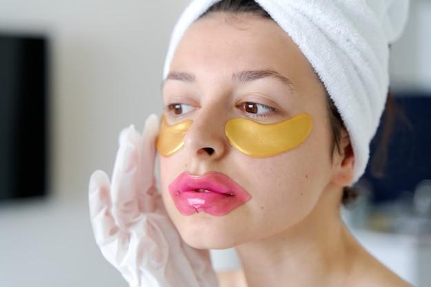Dopo la doccia, una ragazza avvolta in un asciugamano utilizza cerotti cosmetici per la pelle sotto gli occhi, le labbra e i guanti per idratare mani e piedi. tendenze cosmetiche per la cura del corpo a casa