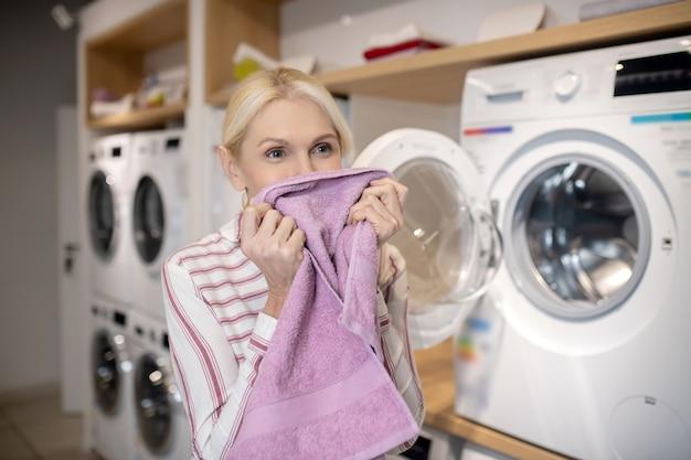 Dopo il lavaggio. donna bionda in camicia a righe che sente l'odore di un asciugamano dopo il lavaggio