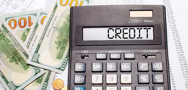 Sullo sfondo di contanti e documenti c'è una calcolatrice nera con il testo credito sul tabellone. concetto di affari