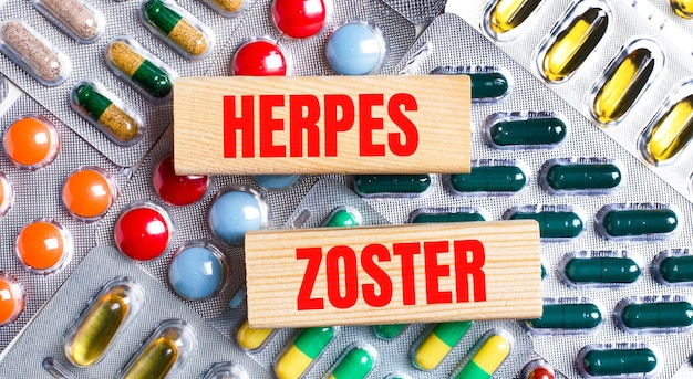 Sullo sfondo di piatti multicolori, blocchi di legno con il testo herpes zoster. concetto medico.