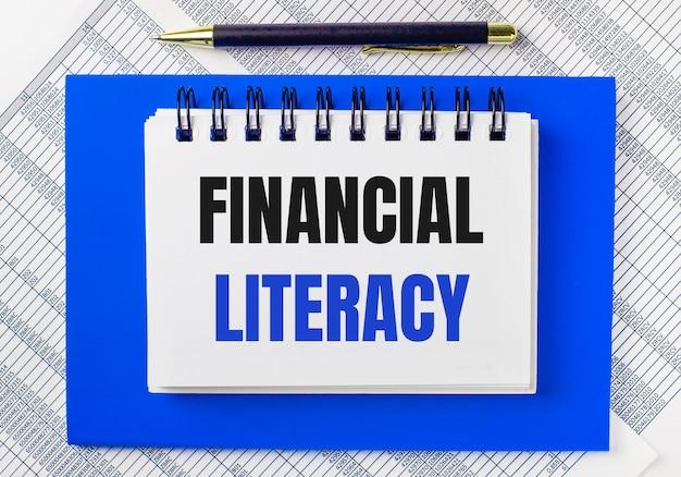 Sullo sfondo dei rapporti sul desktop, un blocco note blu. ha una penna e un taccuino bianco con il testo financial literacy. concetto di affari