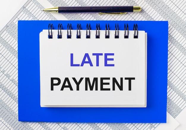 Sullo sfondo dei rapporti sul desktop, un blocco note blu. ha una penna e un taccuino bianco con la scritta pagamento in ritardo. concetto di affari