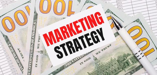 Sullo sfondo di rapporti e dollari: una penna bianca e una carta con il testo strategia di marketing. concetto di affari