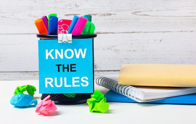 Sullo sfondo chiaro di una parete di legno, c'è un bicchiere con pennarelli colorati, fogli di carta stropicciata e un foglio di carta blu con la scritta conosci le regole.