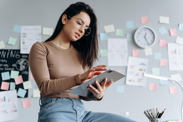 Contro il muro di un muro grigio con adesivi e orari di lavoro, una ragazza d'affari sta lavorando su un tablet