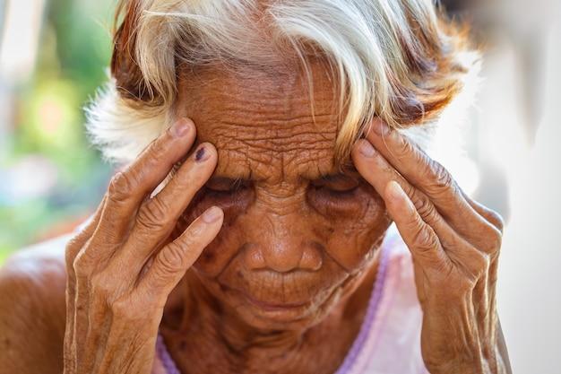 Concetto di età, visione e persone anziane - primo piano di donna asiatica senior viso e occhi, donna senior asiatica con sinusite (sinusite)