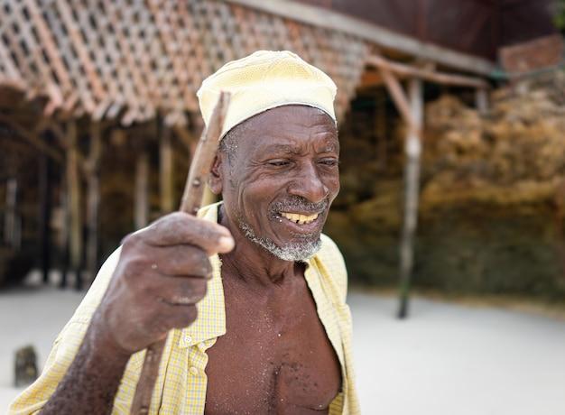 Pastore africano invecchiato che cammina sulla spiaggia tenendo il bastone