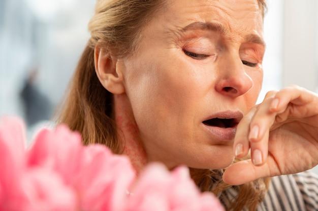Donna piacevole dai capelli biondi invecchiata con le rughe del viso che starnutiscono dopo aver annusato il bouquet