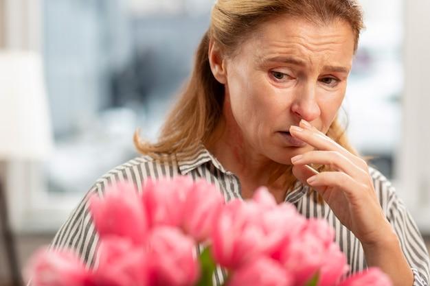 Donna malata dai capelli biondi invecchiata con rughe del viso che si sente male con allergia ai tulipani
