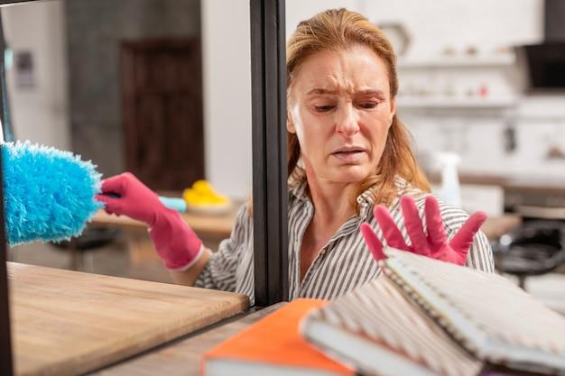 Donna dai capelli biondi invecchiata che indossa guanti che soffre di una forte allergia alla polvere