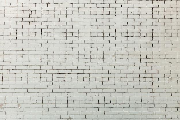Muro di mattoni invecchiato dipinto di bianco con mattoni rossi struttura orizzontale del muro di mattoni del fondo