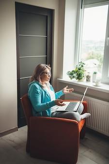 Donna caucasica invecchiata con gli occhiali che parla al computer portatile con qualcuno e spiega mentre era seduto sulla poltrona vicino alla finestra