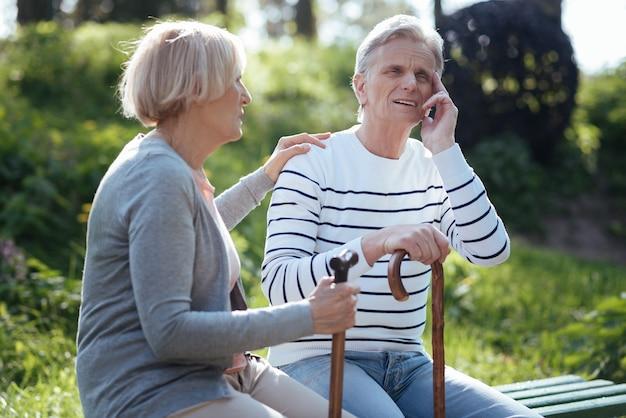 Coppia utile concentrata invecchiata che si sente male e si sostiene a vicenda mentre soffre di mal di testa e si siede nel parco