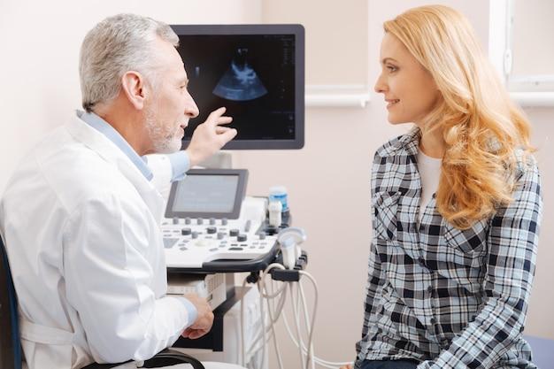 Ecografista esperto e contento invecchiato che lavora in ospedale e consulta il paziente mentre fornisce la scansione ecografica del corpo