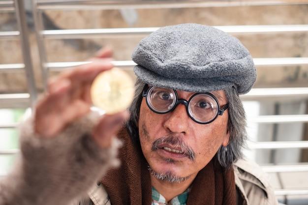 Invecchiato mendicante senzatetto sporco che fissa la moneta d'oro con eccitazione